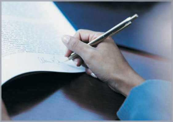 Image of a hand signing a document to symbolize our involvement with corporate and commercial law.