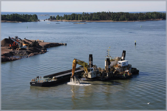 Image of work boats and dredge digging in a harbour to symbolize our involvement with maritime law.