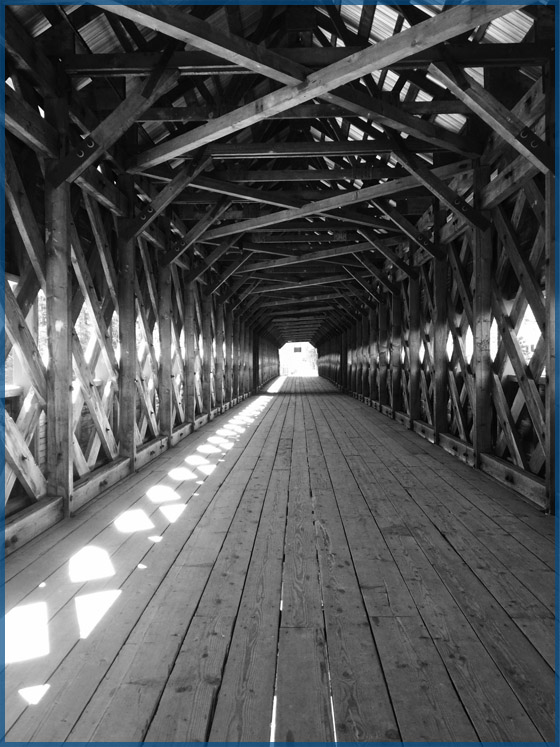 Covered wooden bridge with exposed wooden support beams for the April 2018 newsletter.
