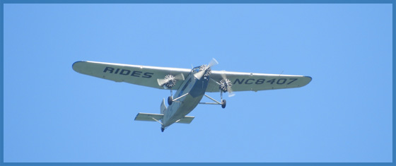 A small triple engine airplane flying in the blue sky for the February 2017 newsletter.
