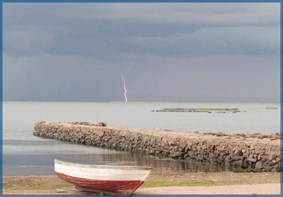 Red and white wooden dory sitting on the shore of a lake while lightning strikes on the horizon for January 2018 newsletter.