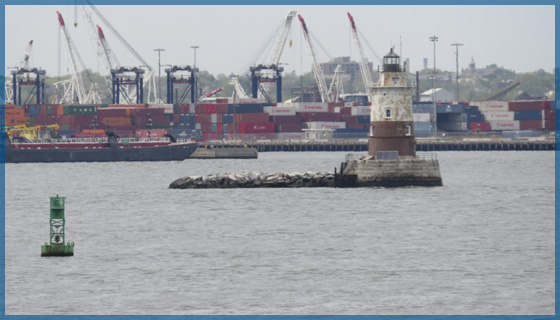 Several container ships loading and off loading in a port with small lighthouse in the harbour for the May 2018 newsletter.