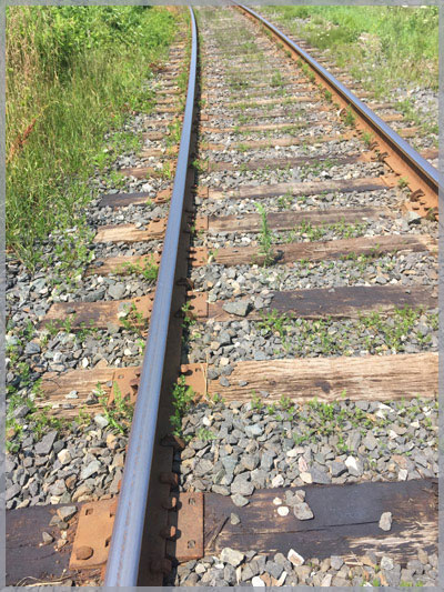 Image of railroad tracks heading off in the distance to symbolize our involvement with railroad law.
